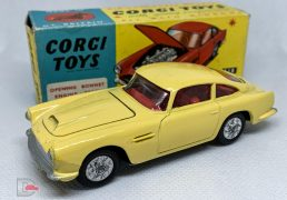 Corgi 218 Aston Martin DB4 - yellow body, red interior, silver trim, open bonnet vent, criss-cross cast hubs - Excellent Plus a beautiful example in a generally Excellent blue and yellow carded picture box