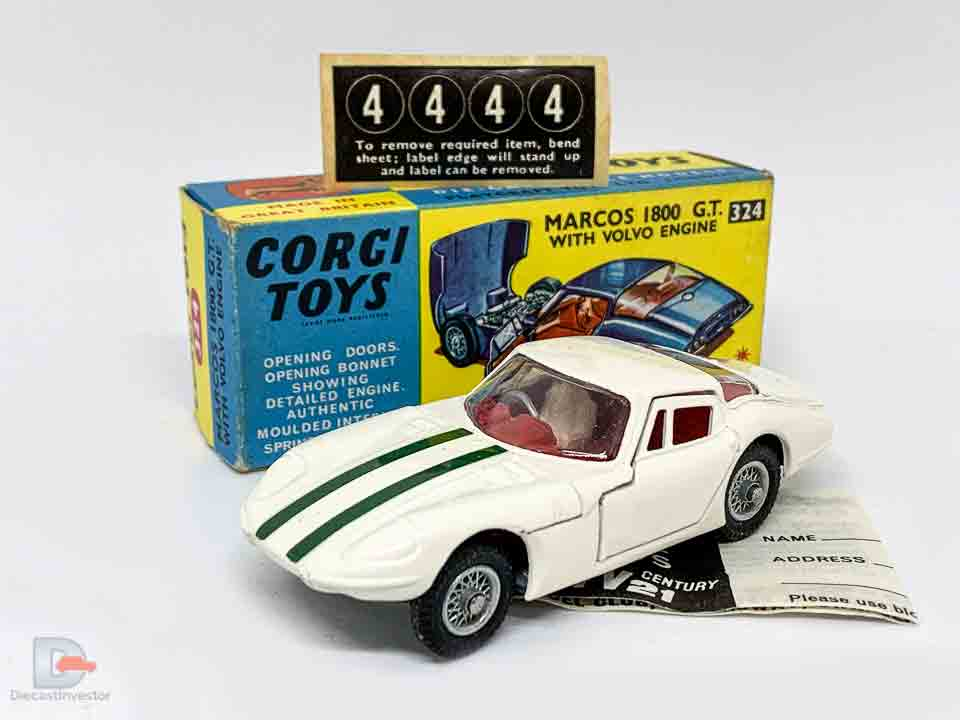 Corgi 324 Marcos 1800 GT - white body with green engine stripes, red interior with figure driver, wire wheels - Excellent Plus still a beautiful example in an Excellent Plus blue and yellow carded picture box - also comes with collectors club folded leaflet and unapplied racing numbers.