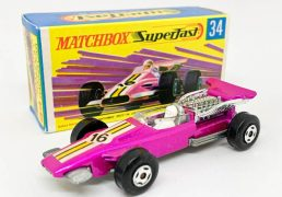 """Matchbox Superfast 34d Formula 1 Racing Car (Superfast 34a) - metallic candy pink body with yellow stripe racing number 16 nose label, clear windscreen, bare metal base, 4-spoke wide wheels - Mint in Near Mint """"New"""" type G box with """"TM""""."""